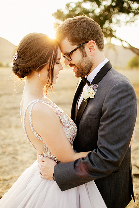 San juan capistrano outdoor wedding at serra plaza bride ruffled ballgown with beaded bodice and straps with open back design and long veil with crystal hairpiece with groom charcoal grey tuxedo with matching vest and white dress shirt with black bow tie and white floral boutonniere hugging