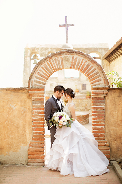 San juan capistrano outdoor wedding at serra plaza bride ruffled ballgown with beaded bodice and straps with open back design and long veil with crystal hairpiece with groom charcoal grey tuxedo with matching vest and white dress shirt with black bow tie and white floral boutonniere hugging holding white and dark purple floral bridal bouquet