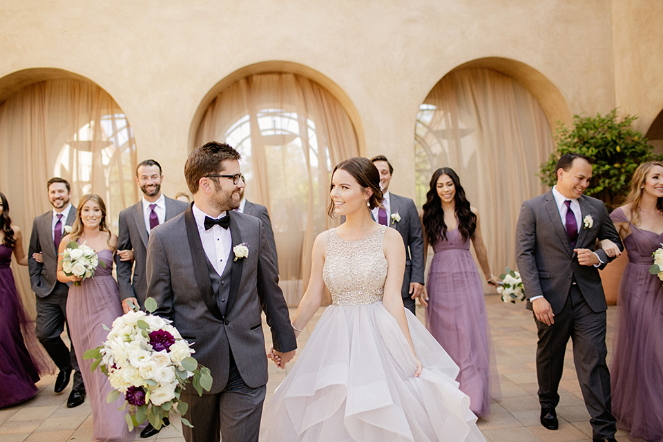 San juan capistrano outdoor wedding at serra plaza bride ruffled ballgown with beaded bodice and straps with open back design and long veil with crystal hairpiece with groom charcoal grey tuxedo with matching vest and white dress shirt with black bow tie and white floral boutonniere holding hands and walking with bridesmaids long purple dresses and groomsmen charcoal suits with long ties