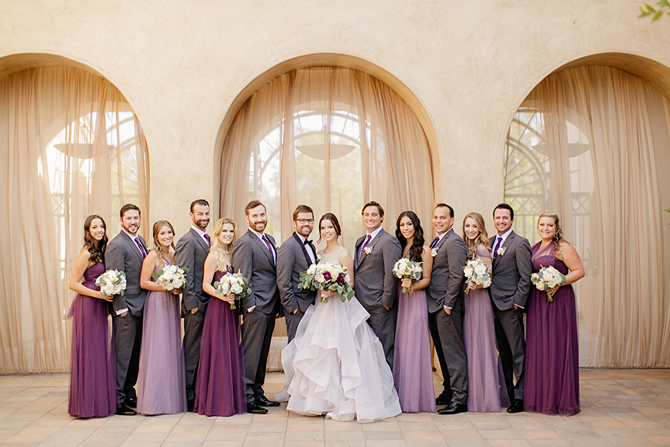 San juan capistrano outdoor wedding at serra plaza bride ruffled ballgown with beaded bodice and straps with open back design and long veil with crystal hairpiece with groom charcoal grey tuxedo with matching vest and white dress shirt with black bow tie and white floral boutonniere holding white and purple floral bridal bouquet with bridesmaids long purple dresses with groomsmen charcoal grey suits holding floral bouquets