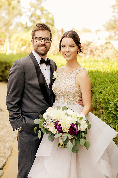 San juan capistrano outdoor wedding at serra plaza bride ruffled ballgown with beaded bodice and straps with open back design and long veil with crystal hairpiece with groom charcoal grey tuxedo with matching vest and white dress shirt with black bow tie and white floral boutonniere hugging and holding white and dark purple floral bridal bouquet