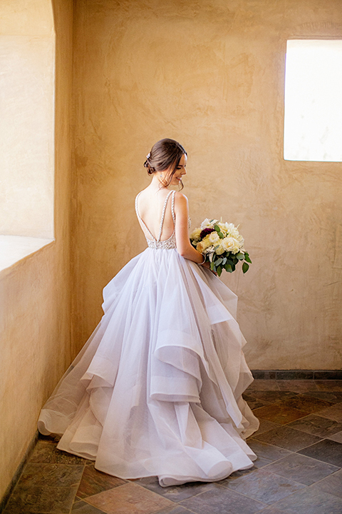 San juan capistrano outdoor wedding at serra plaza bride ruffled ballgown with beaded bodice and straps with open back design and long veil with crystal hairpiece holding white and dark purple floral bridal bouquet