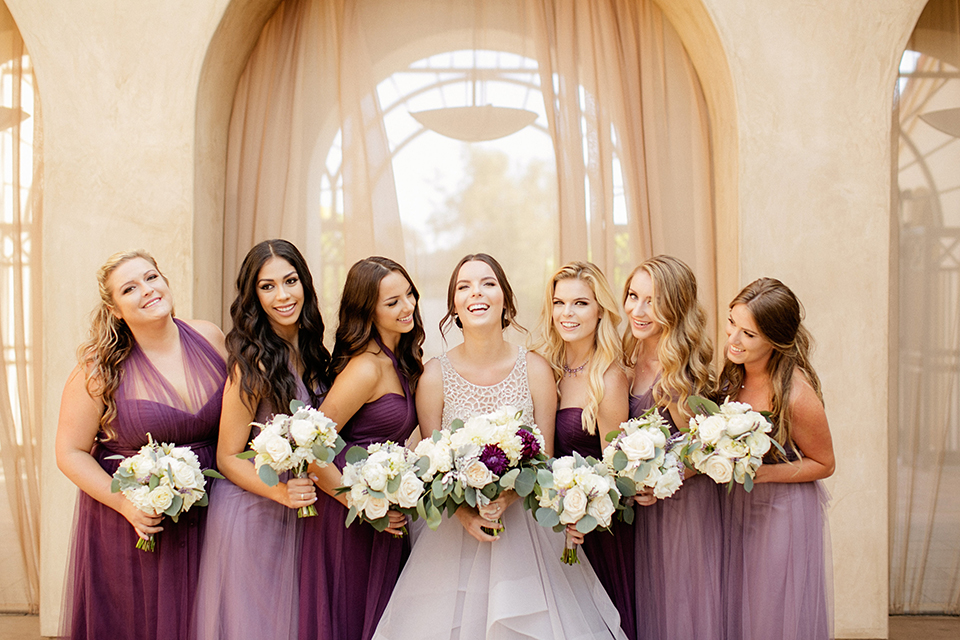San juan capistrano outdoor wedding at serra plaza bride ruffled ballgown with beaded bodice and straps with open back design and long veil with crystal hairpiece holding white and dark purple floral bridal bouquet with bridesmaids long purple dresses with floral bouquets