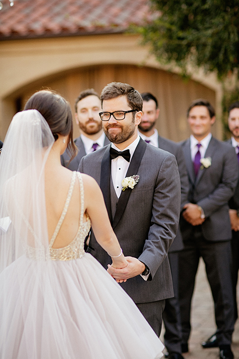 San juan capistrano outdoor wedding at serra plaza bride ruffled ballgown with beaded bodice and straps with open back design and long veil with crystal hairpiece with groom charcoal grey tuxedo with matching vest and white dress shirt with black bow tie and white floral boutonniere holding hands during ceremony