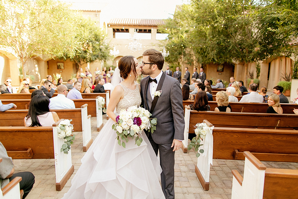 San juan capistrano outdoor wedding at serra plaza bride ruffled ballgown with beaded bodice and straps with open back design and long veil with crystal hairpiece with groom charcoal grey tuxedo with matching vest and white dress shirt with black bow tie and white floral boutonniere kissing after ceremony