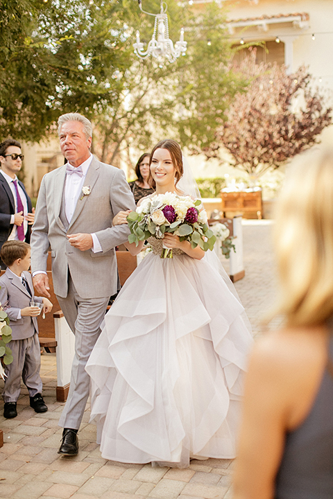 San juan capistrano outdoor wedding at serra plaza bride ruffled ballgown with beaded bodice and straps with open back design and long veil with crystal hairpiece holding white and dark purple floral bridal bouquet walking down the aisle with dad