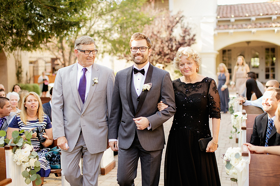 San juan capistrano outdoor wedding at serra plaza groom charcoal grey tuxedo with matching vest and white dress shirt with black bow tie and white floral boutonniere walking down the aisle during ceremony with parents