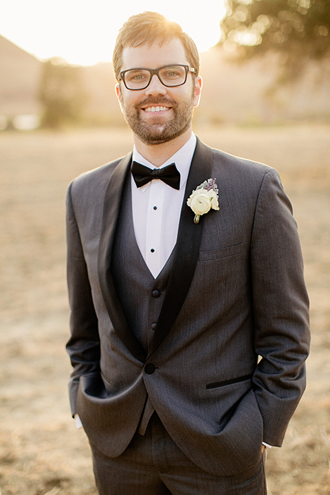San juan capistrano outdoor wedding at serra plaza groom charcoal grey tuxedo with matching vest and white dress shirt with black bow tie and white floral boutonniere standing with hands in pockets