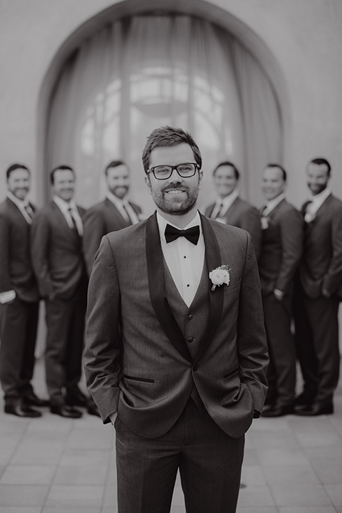 San juan capistrano outdoor wedding at serra plaza groom charcoal grey tuxedo with matching vest and white dress shirt with black bow tie and white floral boutonniere with groomsmen charcoal grey suits with long ties black and white photo