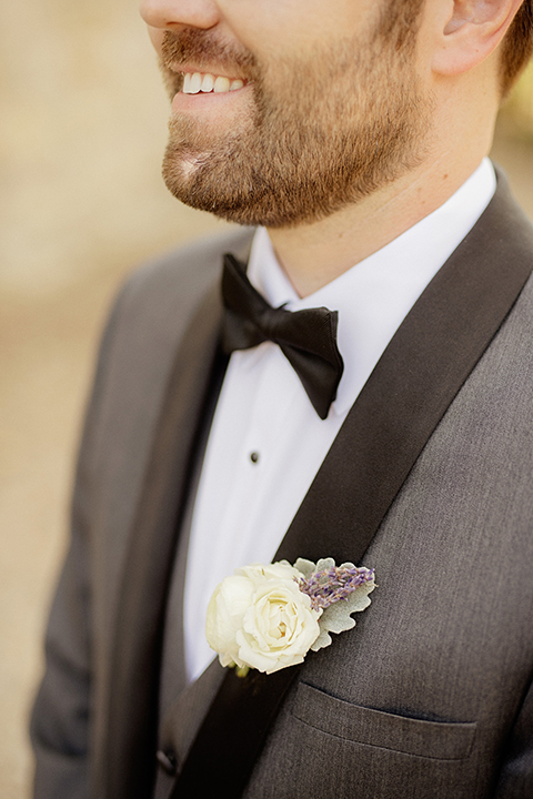 San juan capistrano outdoor wedding at serra plaza groom charcoal grey tuxedo with matching vest and white dress shirt with black bow tie and white floral boutonniere close up