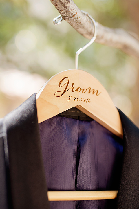 San juan capistrano outdoor wedding at serra plaza groom charcoal grey tuxedo with matching vest and white dress shirt with black bow tie and white floral boutonniere tuxedo coat hanging on personalized hanger