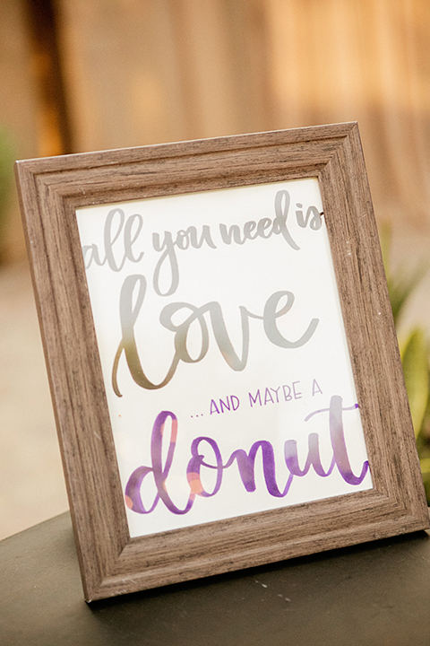 San juan capistrano outdoor wedding at serra plaza reception white and purple calligraphy sign for donuts in light brown wood frame wedding reception decor photo idea