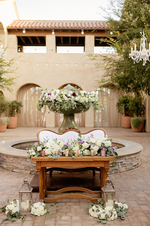 San juan capistrano outdoor wedding at serra plaza reception sweetheart table brown wood table with white and green floral decor with white vintage couch with flower decor on fountain wedding photo idea