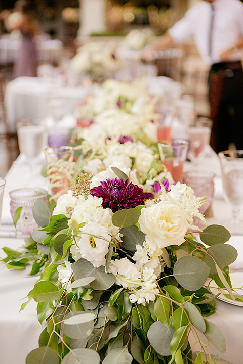 San juan capistrano outdoor wedding at serra plaza reception white table linen with white and dark purple flower centerpiece decor with purple glasses and white place settings