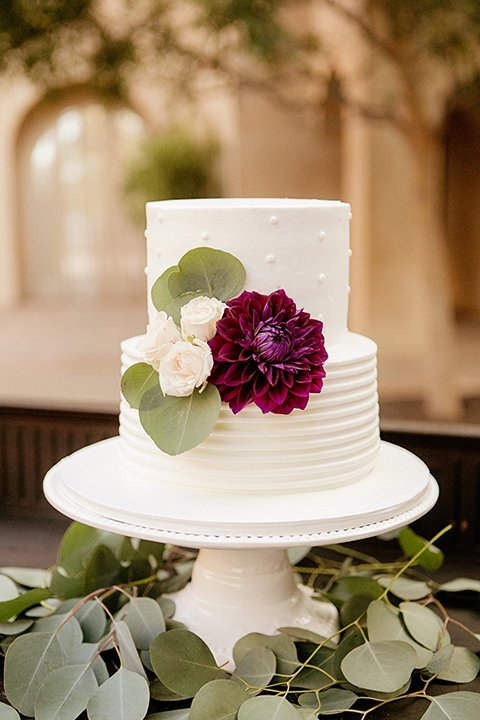 San juan capistrano outdoor wedding at serra plaza reception white two tier wedding cake with white and dark purple flower decor on side with greenery flower decor on bottom sitting on white tray wedding photo idea