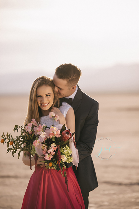 Las vegas engagement shoot in the desert bride white crop top with open back design and pink skirt with groom navy blue suit with matching vest and white dress shirt with black bow tie bride holding floral bridal bouquet
