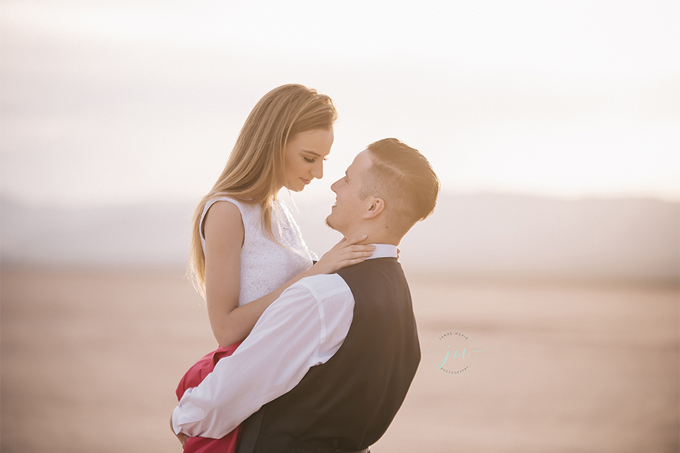 Las vegas engagement shoot in the desert bride white crop top with open back design and pink skirt with groom navy blue suit with matching vest and white dress shirt with black bow tie hugging
