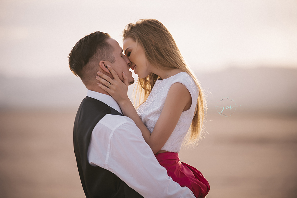 Las vegas engagement shoot in the desert bride white crop top with open back design and pink skirt with groom navy blue suit with matching vest and white dress shirt with black bow tie kissing