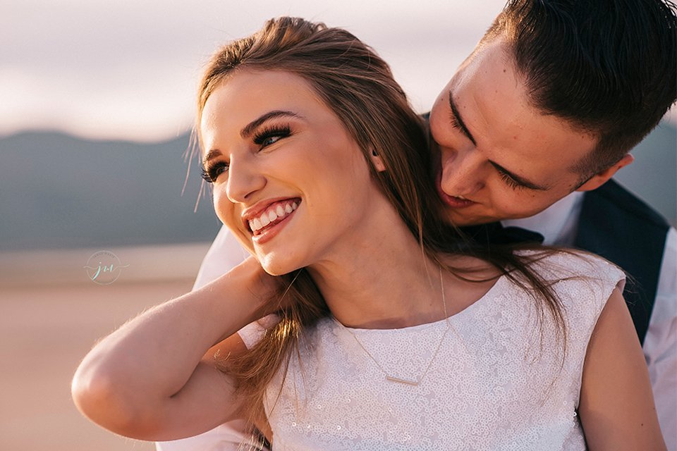 Las vegas engagement shoot in the desert bride white crop top with open back design and pink skirt with groom navy blue suit with matching vest and white dress shirt with black bow tie hugging and smiling