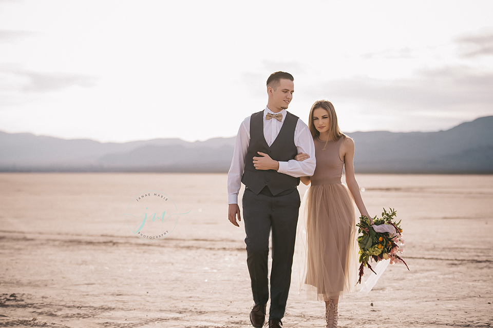 Las vegas engagement shoot bride champagne chiffon dress with high neckline and beaded detail with groom navy blue suit with matching vest and white dress shirt with champagne bow tie bride holding pink and green floral bridal bouquet