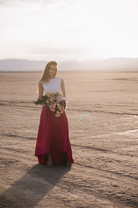 Las vegas engagement shoot in the desert bride white crop top with open back design and pink skirt holding pink and green floral bridal bouquet
