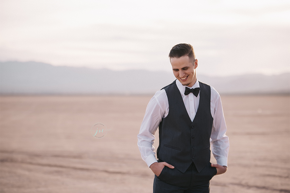 Las vegas engagement shoot groom navy blue suit with matching vest and white dress shirt with black bow tie standing with hands in pockets and no jacket
