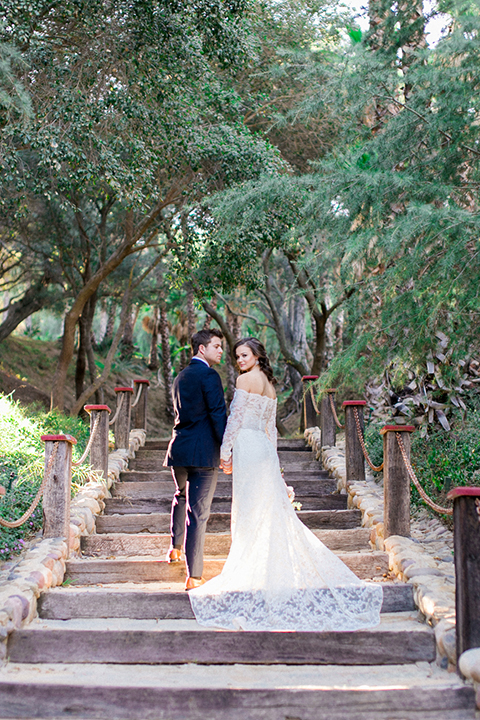 Rancho las lomas outdoor wedding shoot bride lace form fitting gown with off the shoulder long lace sleeves with white flower headpiece decor and groom cobalt blue suit with matching vest and white dress shirt with light blue long striped tie and white floral boutonniere holding hands