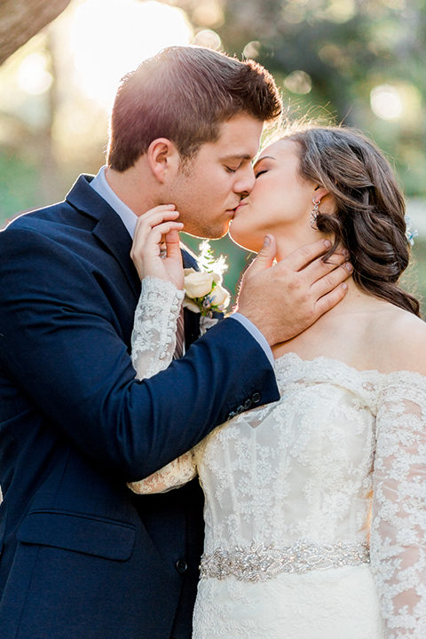 Rancho las lomas outdoor wedding shoot bride lace form fitting gown with off the shoulder long lace sleeves with white flower headpiece decor and groom cobalt blue suit with matching vest and white dress shirt with light blue long striped tie and white floral boutonniere kissing