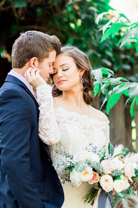 Rancho las lomas outdoor wedding shoot bride lace form fitting gown with off the shoulder long lace sleeves with white flower headpiece decor and groom cobalt blue suit with matching vest and white dress shirt with light blue long striped tie and white floral boutonniere hugging