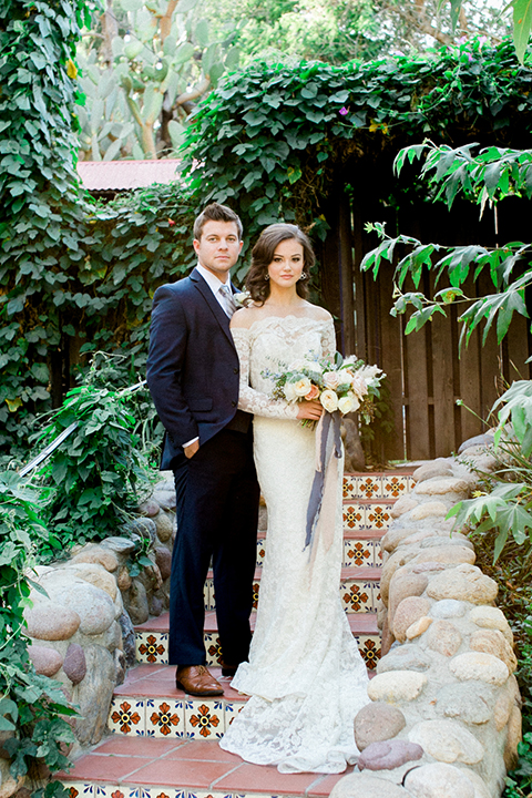 Rancho las lomas outdoor wedding shoot bride lace form fitting gown with off the shoulder long lace sleeves with white flower headpiece decor and groom cobalt blue suit with matching vest and white dress shirt with light blue long striped tie and white floral boutonniere bride holding white floral bridal bouquet