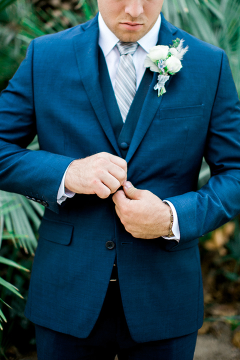 Rancho las lomas outdoor wedding shoot groom cobalt blue suit with matching vest and white dress shirt with light blue long striped tie and white floral boutonniere buttoning jacket