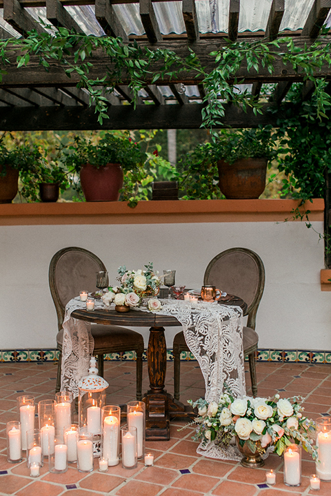 Rancho las lomas outdoor wedding shoot sweetheart table dark brown wood table with white lace table runner and white flower decor with white candles on ground and copper place setting decor