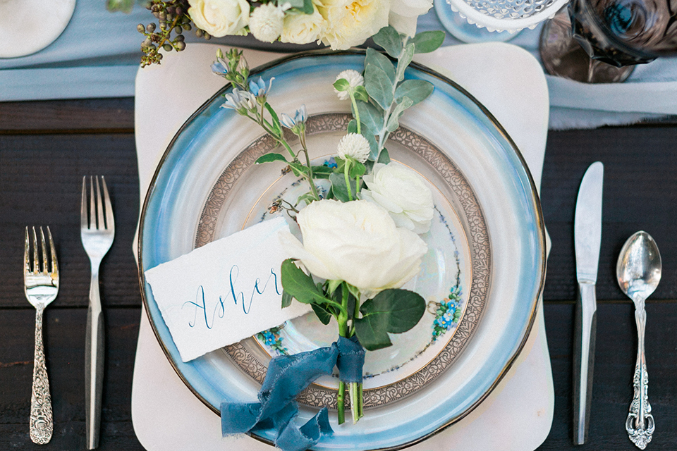 Rancho las lomas outdoor wedding shoot dark brown wood table with long bench and light blue table runner with blue and white place settings and white flower centerpiece decor with matching chairs