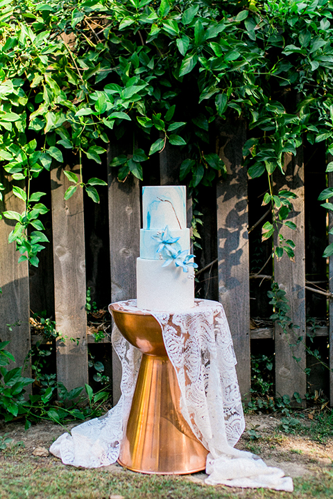 Rancho las lomas outdoor wedding shoot three tier white and blue design wedding cake on copper table stand with white lace linen decor and blue flower decor wedding photo idea for cake