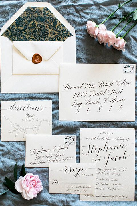 Rancho las lomas outdoor wedding shoot white wedding invitations with black calligraphy writing and red stamp seal on light blue silk linen background wedding photo idea for simple invitations