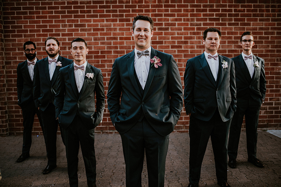 Rustic orange county wedding at the estate on second groom navy blue suit with white dress shirt and tan bow tie with white trim and pink floral boutonniere with groomsmen navy blue suits with light blush pink bow ties