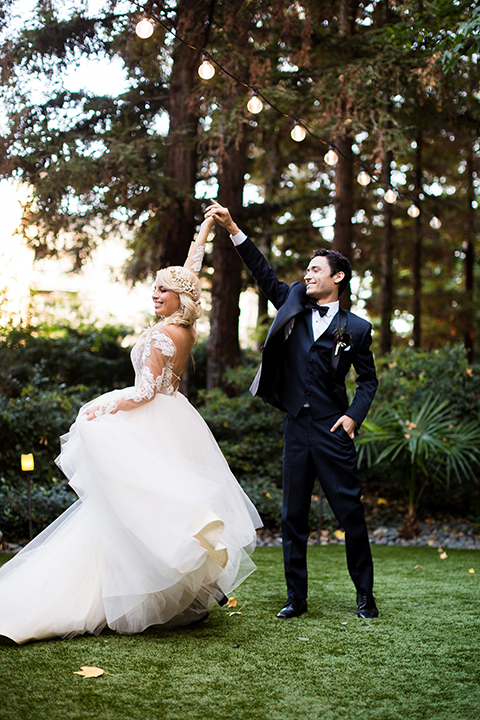 Orange county outdoor wedding shoot at avenue of the arts hotel bride tulle ball gown with lace bodice and lace sleeves with sweetheart illusion neckline and long veil with groom navy blue tuxedo with matching vest and white dress shirt and black bow tie with white pocket square dancing