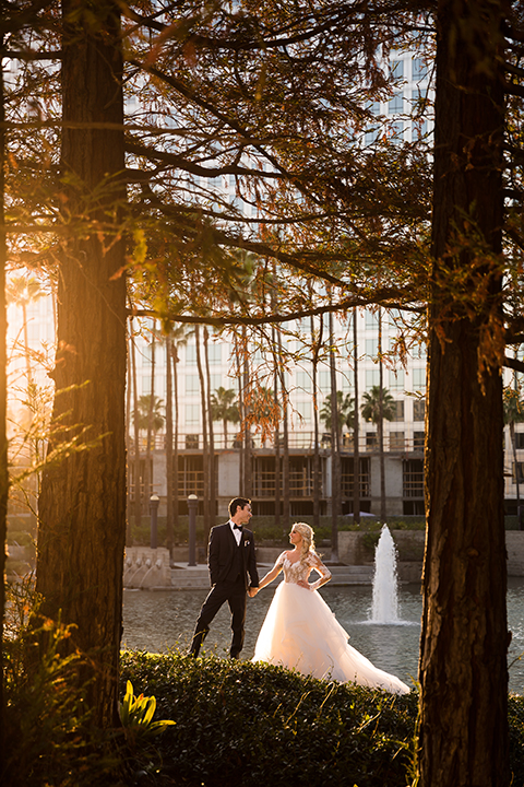 Orange county outdoor wedding shoot at avenue of the arts hotel bride tulle ball gown with lace bodice and lace sleeves with sweetheart illusion neckline and long veil with groom navy blue tuxedo with matching vest and white dress shirt and black bow tie with white pocket square holding hands