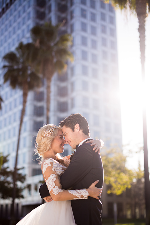 Orange county outdoor wedding shoot at avenue of the arts hotel bride tulle ball gown with lace bodice and lace sleeves with sweetheart illusion neckline and long veil with groom navy blue tuxedo with matching vest and white dress shirt and black bow tie with white pocket square hugging