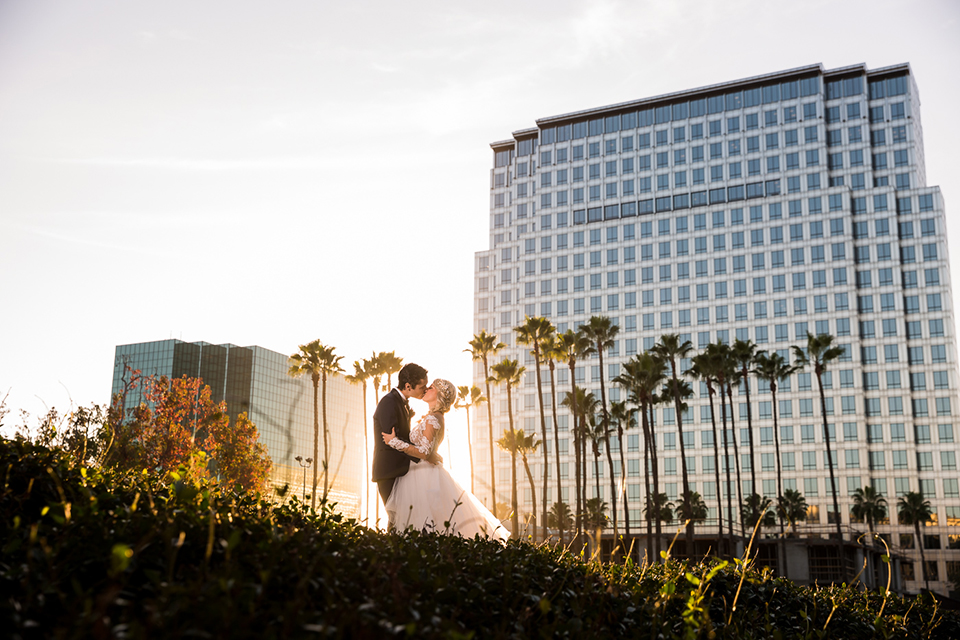 Orange county outdoor wedding shoot at avenue of the arts hotel bride tulle ball gown with lace bodice and lace sleeves with sweetheart illusion neckline and long veil with groom navy blue tuxedo with matching vest and white dress shirt and black bow tie with white pocket square kissing