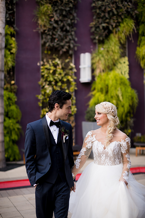 Orange county outdoor wedding shoot at avenue of the arts hotel bride tulle ball gown with lace bodice and lace sleeves with sweetheart illusion neckline and long veil with groom navy blue tuxedo with matching vest and white dress shirt and black bow tie with white pocket square holding hands and walking