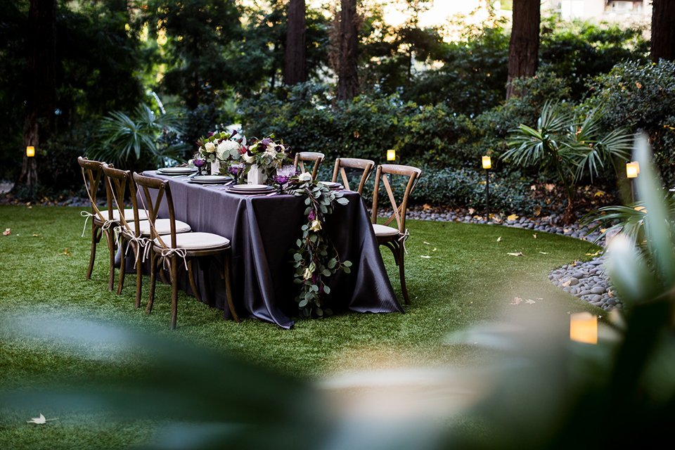 Orange county outdoor wedding shoot at avenue of the arts hotel table set up with light purple linen and white place settings with white and purple floral centerpiece decor and purple glasses with brown wooden chairs