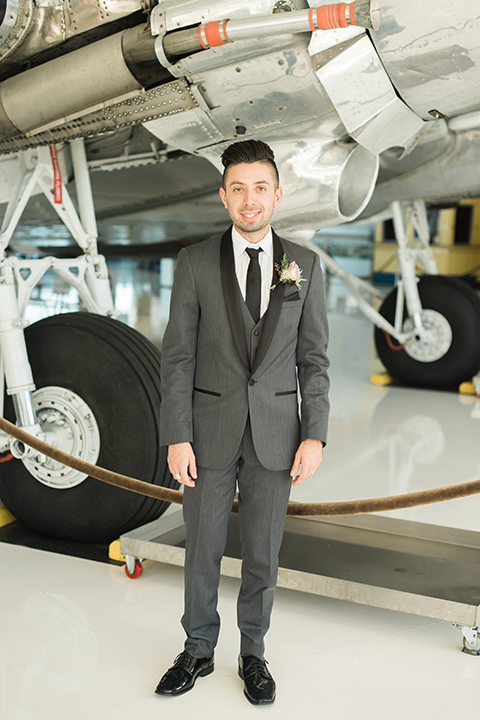 Orange county same sex wedding shoot at lyon air museum groom grey tuxedo with matching vest and white dress shirt with long black tie and white floral boutonniere