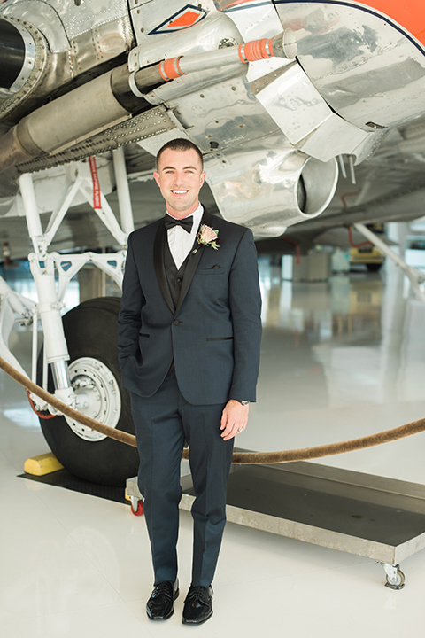 Orange county same sex wedding shoot at lyon air museum groom navy tuxedo with matching vest and white dress shirt with black bow tie and white floral boutonniere