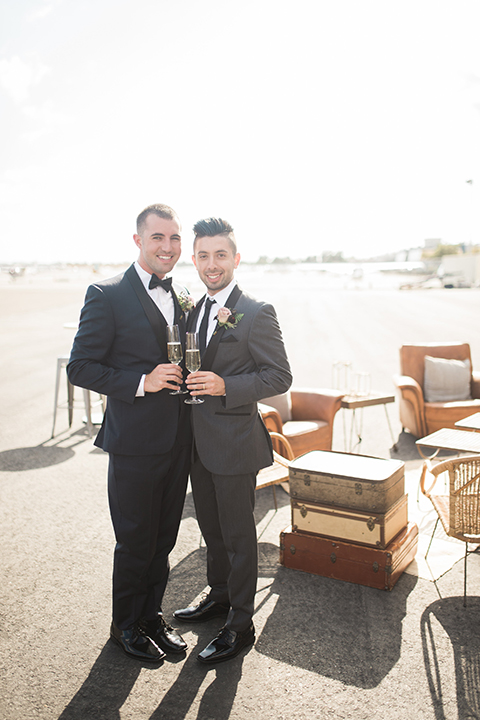 Orange county same sex wedding shoot at lyon air museum groom navy tuxedo with matching vest and white dress shirt with black bow tie and groom grey tuxedo with matching vest and white dress shirt with long black tie holding drinks