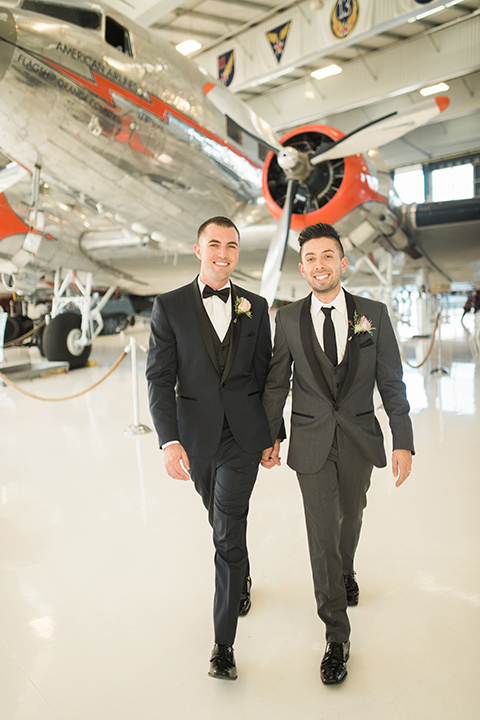 Orange county same sex wedding shoot at lyon air museum groom navy tuxedo with matching vest and white dress shirt with black bow tie and groom grey tuxedo with matching vest and white dress shirt with long black tie walking and holding hands