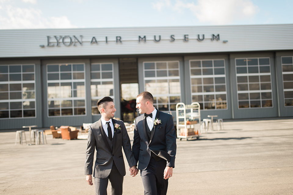 Orange county same sex wedding shoot at lyon air museum groom navy tuxedo with matching vest and white dress shirt with black bow tie and groom grey tuxedo with matching vest and white dress shirt with long black tie walking and holding hands outside