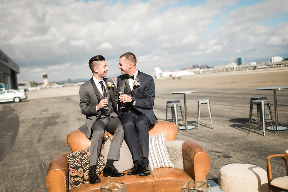 Orange county same sex wedding shoot at lyon air museum groom navy tuxedo with matching vest and white dress shirt with black bow tie and groom grey tuxedo with matching vest and white dress shirt with long black tie sitting on couch holding drinks