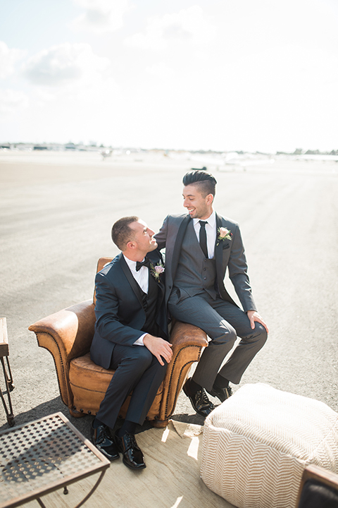 Orange county same sex wedding shoot at lyon air museum groom navy tuxedo with matching vest and white dress shirt with black bow tie and groom grey tuxedo with matching vest and white dress shirt with long black tie sitting in chair