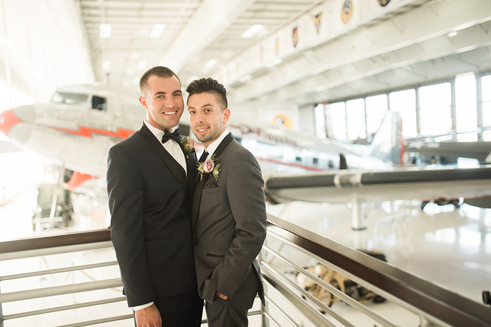 Orange county same sex wedding shoot at lyon air museum groom navy tuxedo with matching vest and white dress shirt with black bow tie and groom grey tuxedo with matching vest and white dress shirt with long black tie